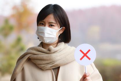 マスクを着け×札を持つ女性
