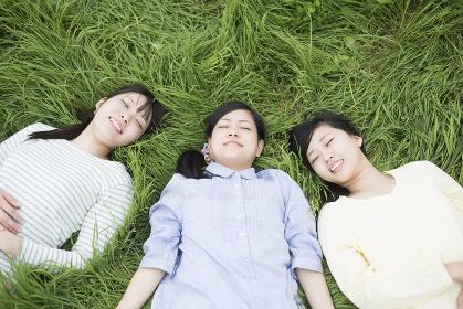 草原に寝転ぶ3人の女性