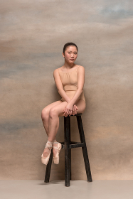 Tired ballet dancer sitting on the wooden chair on a pink background