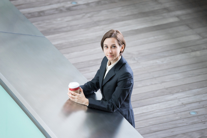 テイクアウトコーヒーを飲む女性