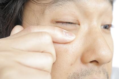 目を擦る日本人男性