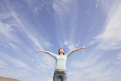 青空の下で両手を広げて深呼吸する女性