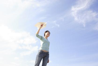 爽やかな青空の下で紙飛行機を飛ばす若い女性
