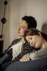 寄り添って眠る若い夫婦