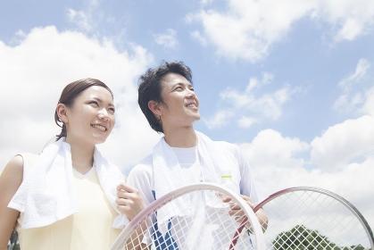 テニスラケットを持つ男女