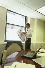 オフィスで新聞を読むビジネスマン