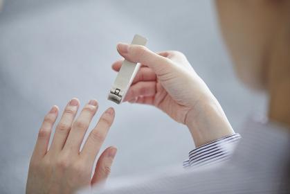 爪切りで爪を切る女性の手元
