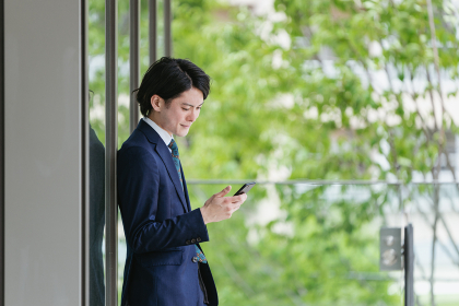 スマートフォンを見る若い男性・ビジネスマンが出社してIoTをするイメージ