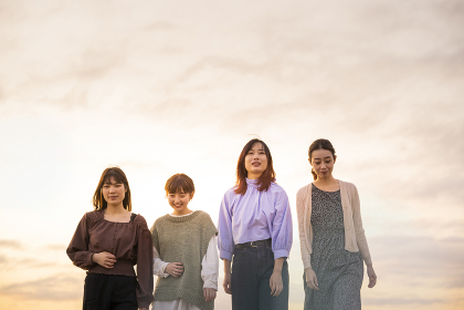 夕暮れの中、寄り添って海沿いを歩く女性4人