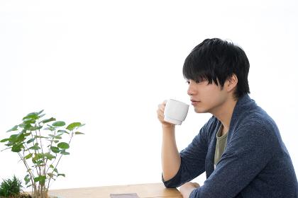 カフェでホットドリンクを飲む男性
