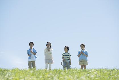 草原で楽器を持ち微笑む小学生