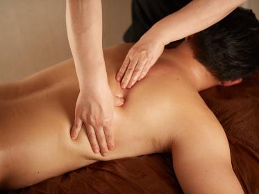 背中のマッサージを受けるアジア人男性