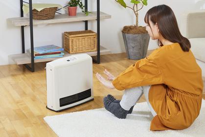 ガスファンヒーターで体を温める日本人女性