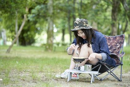 一人キャンプで料理をする若い日本人女性
