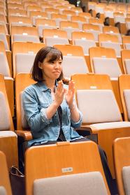 コンサートホールの椅子に座る1人の女性(拍手)