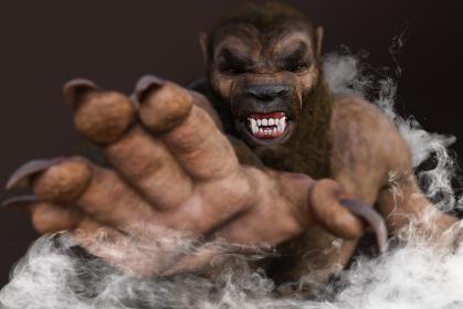 毛深く牙を剥く狼男が鋭く尖った爪のある大きな手でつかみかかろうとする