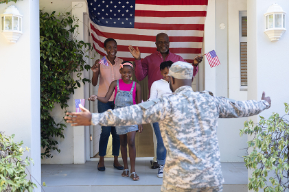 African american soldier father with wife, children and father greeting him outside their house. soldier returning home to family.