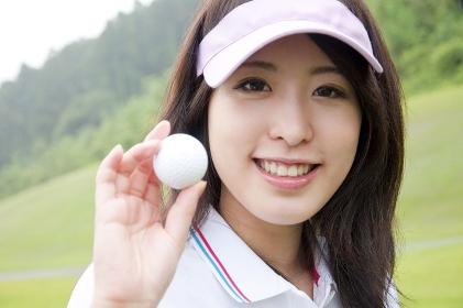 ゴルフボールを持って微笑む女性