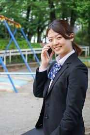笑顔でスマホを使う制服姿の学生