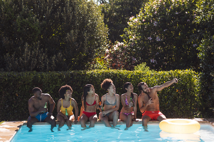 Diverse group of friends drinking beer and sitting at the poolside talking. Hanging out and relaxing outdoors in summer.