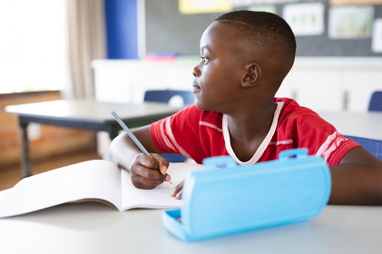 African american boy studying while sitting on his desk in the class at school. school and education concept