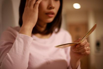 貯金通帳を見て悩む女性