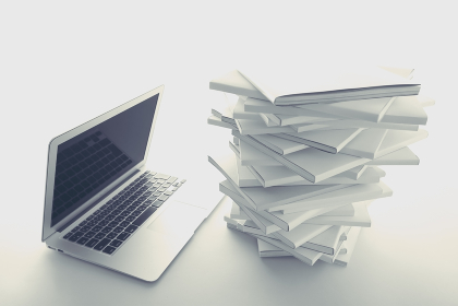 積み重ねた白い本とノートパソコン