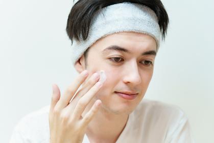 顔にクリームを塗る若い男性