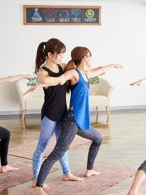 ヨガのポーズを指導するアジア人女性インストラクター