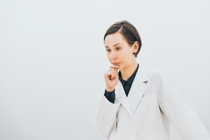 考えるショートヘアーの女性(白衣着用)