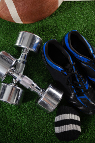 High angle view of dumbbells by sports shoe and American football