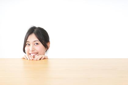 テーブルから顔を出す女性
