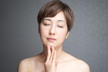 顎に手を当てる目をつぶる中年の日本人女性
