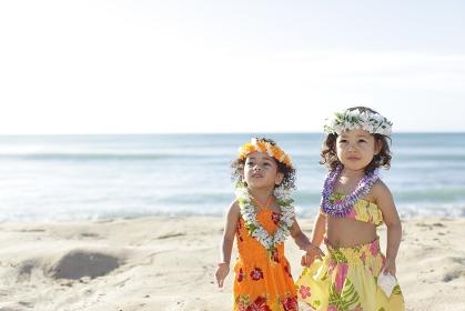 海岸でフラダンスの衣装を着たハーフの女の子達