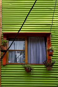 orange wood window and a green metal wall in la boca buenos aires argentina