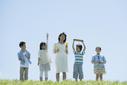 草原で楽器を持ち微笑む小学生と先生
