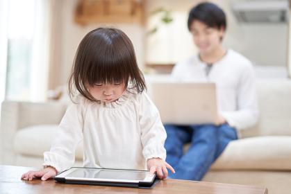 自宅で仕事をするパパと、1人でタブレットを見るアジア人の子供