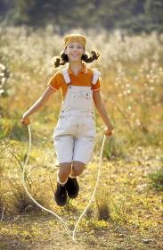 Maedchen mit braunen Zoepfen und gelbem Kopftuch, 12 Jahre, bekleidet mit orange farbenem Polo Shirt und kurzer weisser Latzhose springt vor einem gelben Kornfeld Seilchen