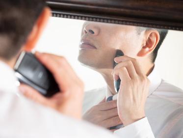 鏡を見ながら急いでひげを剃る男性ビジネスマン