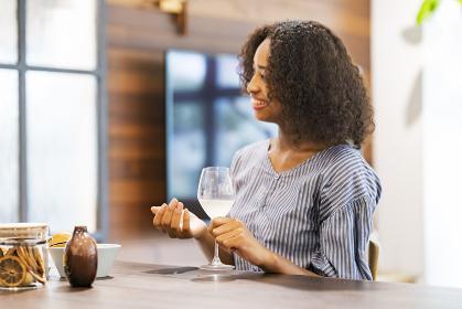 ワイングラスを手に笑顔で談笑する若い女性
