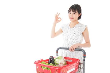 スーパーでOKサインをする若い女性