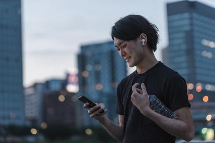 屋外で音楽を聞きながらランニングの準備をする若い男性