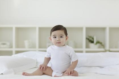 ベッドの上でお座りをしている赤ちゃん