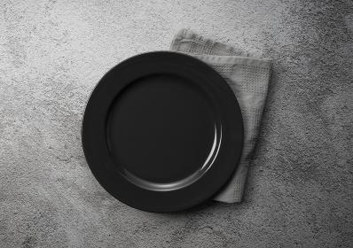 石の背景に黒いお皿と布巾