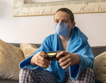 During the pandemic of the COVID-19 boy playing at home with a console