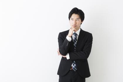 腕を組んで考える若いビジネスマン