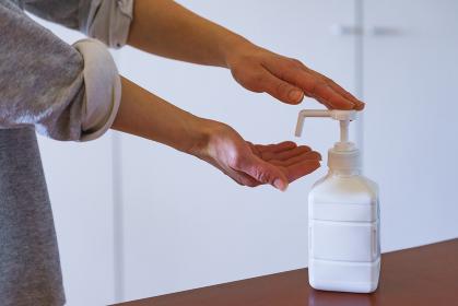 アルコールで手を消毒する中年女性【ニューノーマルのライフスタイル】