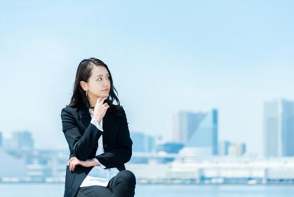 腕組みをして考える女性・ビジネスイメージ