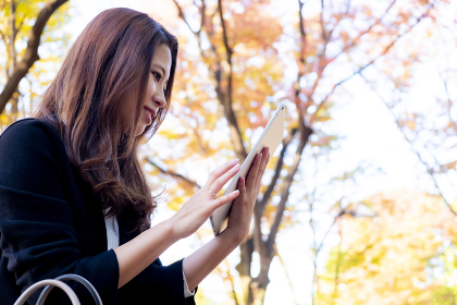 【東京都】屋外でスマホを見る女性【2020年 紅葉】