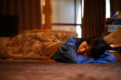 こたつで居眠りする女性